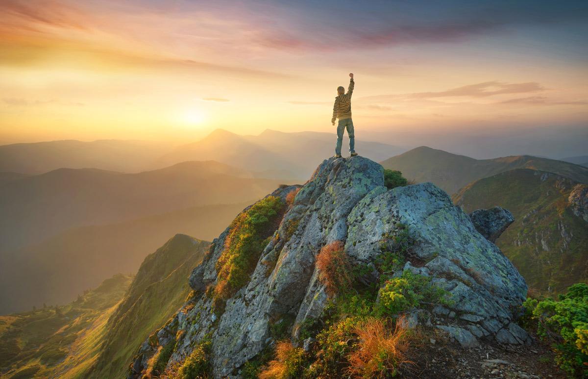 Homme victorieux au sommet d'une montagne