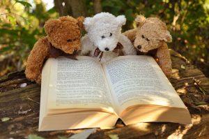Trois ours en peluche lisant un livre dans l'herbe
